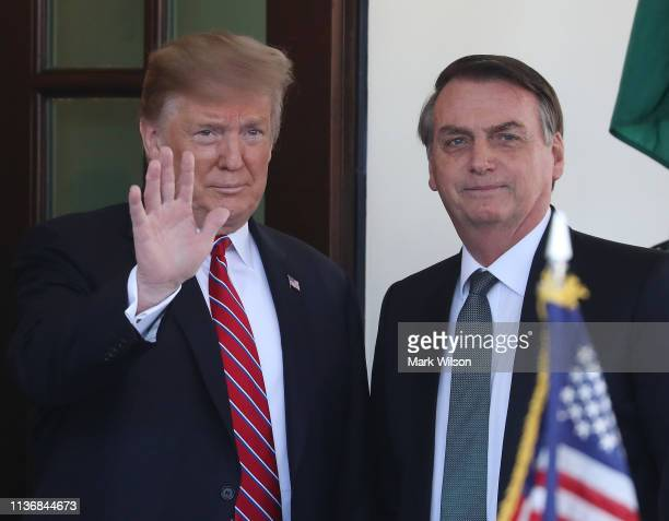S President Donald Trump greets Brazilian President Jair Bolsonaro upon his arrival at the West Wing of the White House March 19 2019 in Washington...