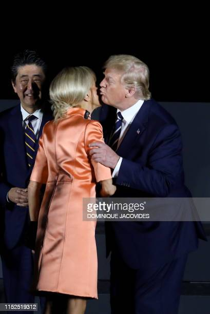 President Donald Trump greets French President's wife Brigitte Macron next to Japan's Prime Minister Shinzo Abe as they pose for a group photo during...