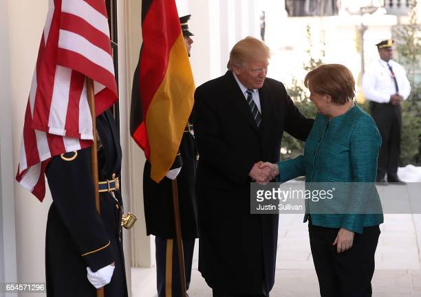 S President Donald Trump greets German Chancellor Angela Merkel as she arrives to the White House on March 17 2017 in Washington DC