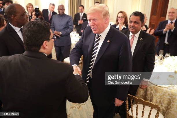 S President Donald Trump greets guests while hosting an Iftar dinner in the State Dining Room at the White House June 6 2018 in Washington DC The...