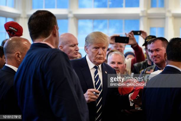 US President Donald Trump greets guests while meeting with supporters during a Bikers for Trump event at the Trump National Golf Club August 11 2018...
