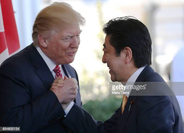 President Donald Trump greets Japanese Prime Minister Shinzo Abe as he arrives at the White House on February 10 2017 in Washington DC The two will...