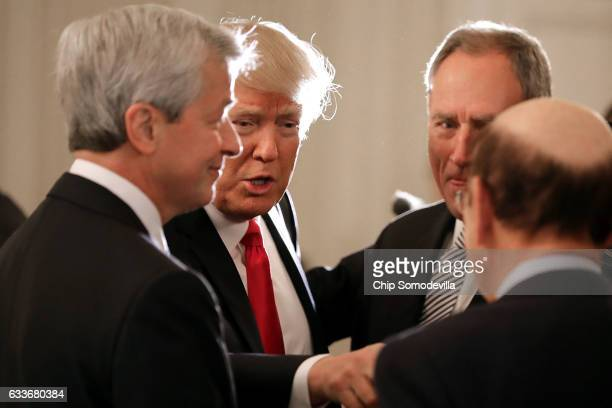 S President Donald Trump greets JPMorgan Chase CEO Jamie Dimon and other guests at the beginning of a policy forum in the State Dining Room at the...
