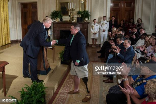 President Donald Trump greets Michael Verardo who lost his leg in Afghanistan serving as a Sergeant in the 82nd Airborne Division in 2010 during a...