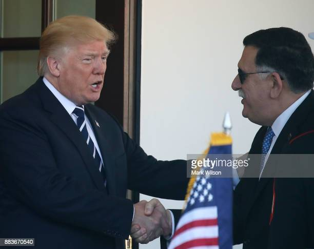 President Donald Trump greets Prime Minister Fayez al-Sarraj of Libya upon his arrival for a meeting at the West Wing of the White House on December...