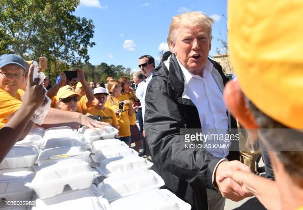 US President Donald Trump greets residents beside a table of prepared meals September 19 2018 in New Bern North Carolina as he tours areas of the...