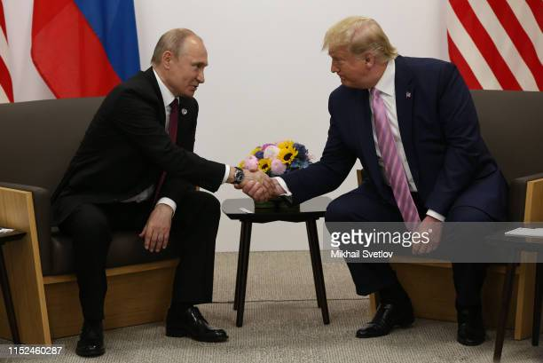 President Donald Trump greets Russian President Vladimir Putin during their bilateral meeting at the G20 Osaka Summit 2019, in Osaka, Japan, June...