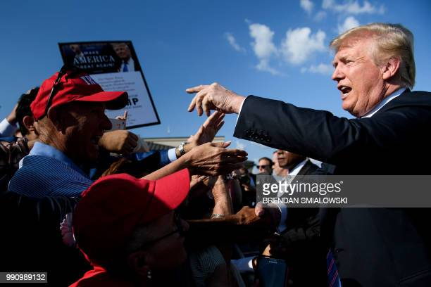US President Donald Trump greets supporters as he arrives at Greenbrier Valley Airport on July 3 2018 in Lewisburg West Virginia Trump will speak at...