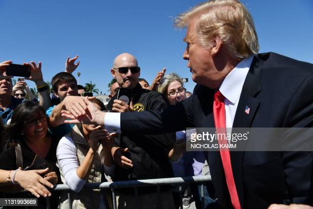US President Donald Trump greets supporters as he arrives at Palm Beach International Airport in Florida on March 22 2019