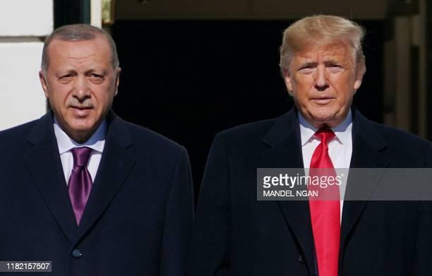 US President Donald Trump greets Turkey's President Recep Tayyip Erdoan upon arrival outside the White House in Washington DC on November 13 2019...