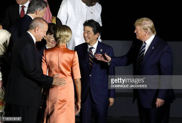 US President Donald Trump greets Turkey's president Recep Tayyip Erdogan next to Japan's Prime Minister Shinzo Abe and his wife Akie as they pose for...