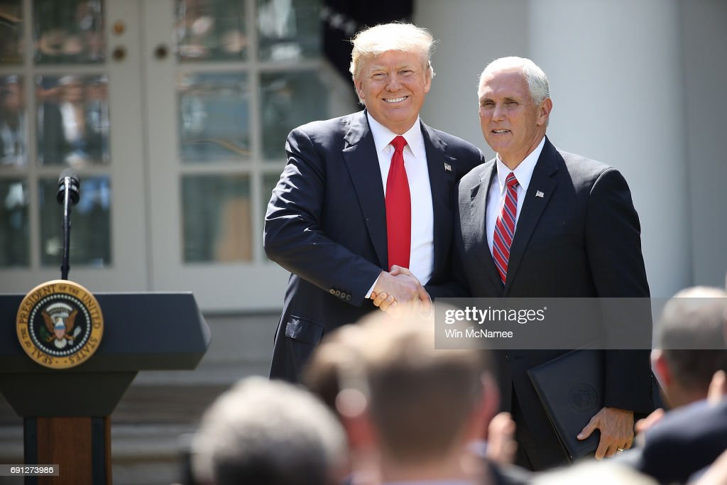 U.S. President Donald Trump greets U.S. Vice President Mike Pence before announcing his decision for the United States to pull out of the Paris climate agreement in the Rose Garden at the White House June 1, 2017 in Washington, DC. Trump pledged on the campaign trail to withdraw from the accord, which former President Barack Obama and the leaders of 194 other countries signed in 2015. The agreement is intended to encourage the reduction of greenhouse gas emissions in an effort to limit global warming to a manageable level.