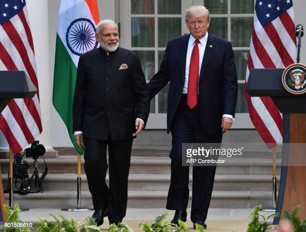 US President Donald Trump guides Indian Prime Minister Narendra Modi towards a joint press conference in the Rose Garden at The White House in...