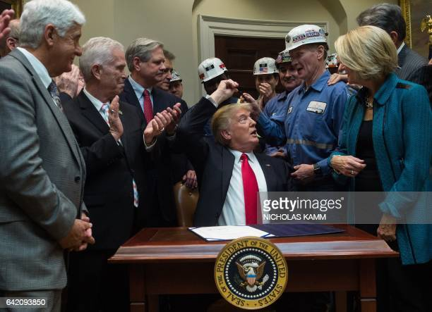 President Donald Trump hands coal miners the pen he used to sign a bill eliminating regulations on the mining industry in the Roosevelt Room at the...