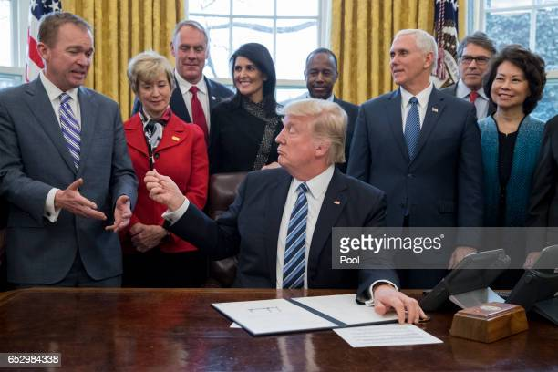 President Donald Trump hands his pen to Director of the Office of Management and Budget Mick Mulvaney , after signing an executive order entitled,...