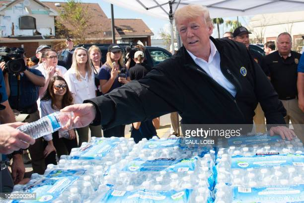 US President Donald Trump hands out bottles of water as they tour damage from Hurricane Michael in Lynn Haven Florida October 15 2018 President...