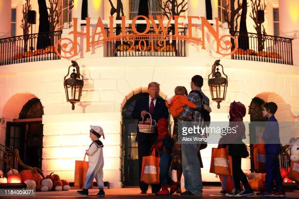 S President Donald Trump hands out candy to children as they trickortreat during a Halloween at the White House event at the South Portico of the...