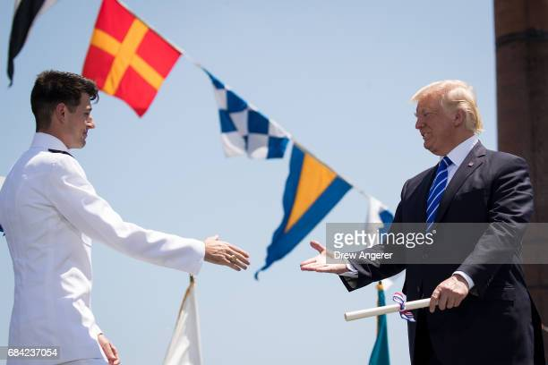 President Donald Trump hands out diplomas to Coast Guard cadets at the commencement ceremony at the US Coast Guard Academy May 17 2017 in New London...