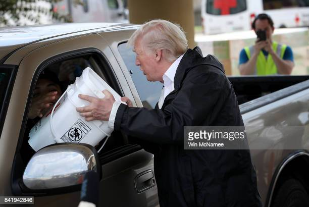 S President Donald Trump hands out emergency supplies to residents impacted by Hurricane Harvey while visiting the First Church of Pearland September...