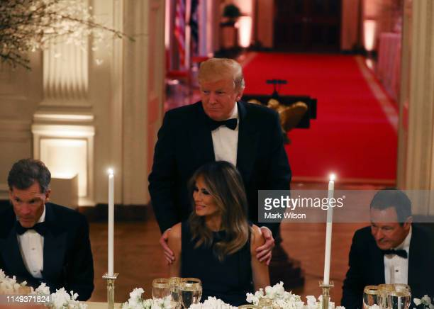 S President Donald Trump helps first lady Melania Trump to her seat during the White House Historical Association Dinner in the East Room of the...
