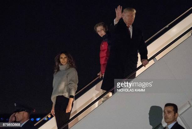 US President Donald Trump his son Barron and First Lady Melania Trump step off Air Force One at Andrews Air Force Base in Maryland on November 26...