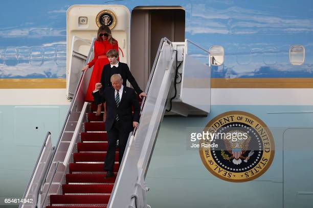 President Donald Trump his wife Melania Trump and their son Barron Trump arrive together on Air Force One at the Palm Beach International Airport to...