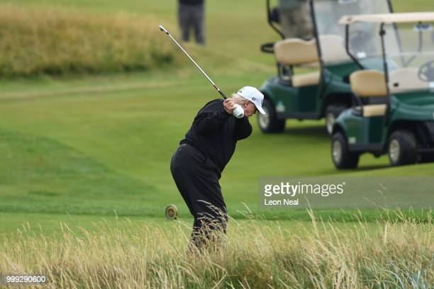 S President Donald Trump hits a tee shot whilst playing a round of golf at Trump Turnberry Luxury Collection Resortduring the US President's first...