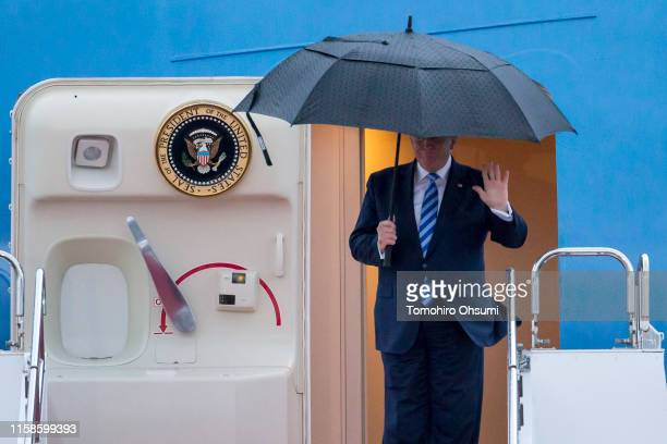 President Donald Trump holding an umbrella waves as he arrives at the Osaka International Airport for the G-20 Summit on June 27, 2019 in Osaka,...