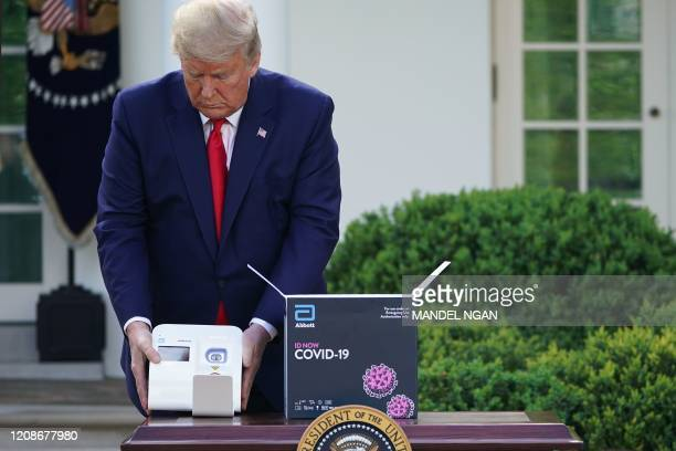 President Donald Trump holds a 5-minute test for COVID-19 from Abbott Laboratories during the daily briefing on the novel coronavirus, COVID-19, in...