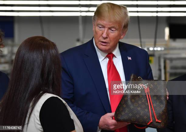 President Donald Trump holds a bag during a visit to the new Louis Vuitton factory in Alvarado , Johnson County, Texas on October 17, 2019. - A...