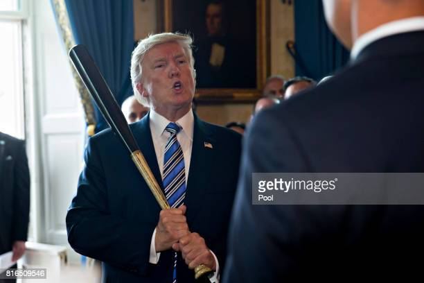US President Donald Trump holds a baseball bat while participating in a Made in America event with companies from 50 states featuring their products...
