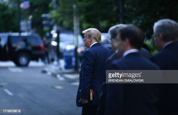 US President Donald Trump holds a bible as he walks through Lafayette Park after spending time in front of St John's Episcopal church in Washington...