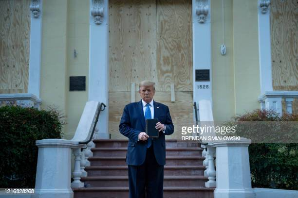 US President Donald Trump holds a Bible while visiting St John's Church across from the White House after the area was cleared of people protesting...