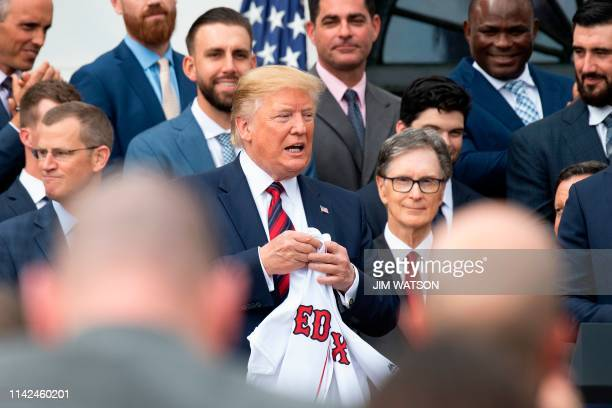 US President Donald Trump holds a Boston Redsox's jersey that was given to him as he welcomed the 2018 World Series Champions to the White House in...