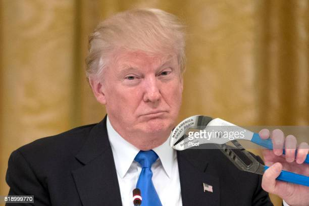 US President Donald Trump holds a Channellock tool engraved with his name and Make America Great Again during a meeting with US company...