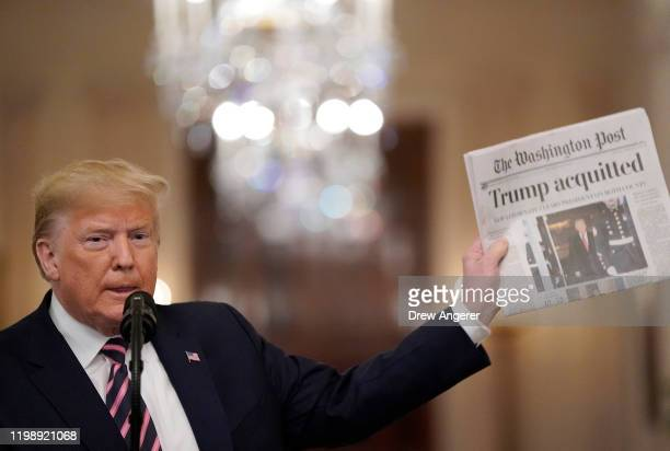 S President Donald Trump holds a copy of The Washington Post as he speaks in the East Room of the White House one day after the US Senate acquitted...