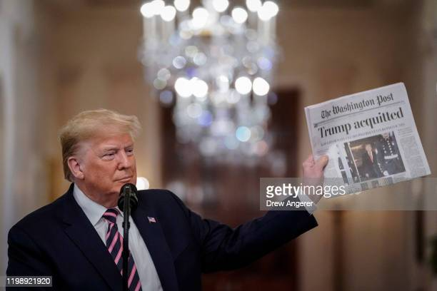 President Donald Trump holds a copy of The Washington Post as he speaks in the East Room of the White House one day after the U.S. Senate acquitted...