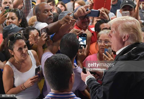 US President Donald Trump holds a flashlight during a visit to the Cavalry Chapel in Guaynabo Puerto Rico on October 3 2017 Nearly two weeks after...