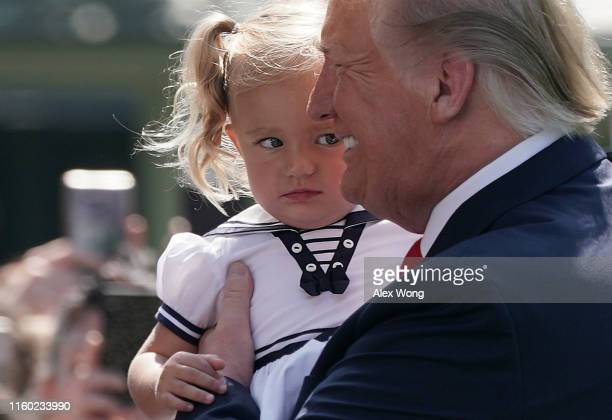 S President Donald Trump holds a girl prior to his departure from the White House July 5 2019 in Washington DC President Trump and the first lady...
