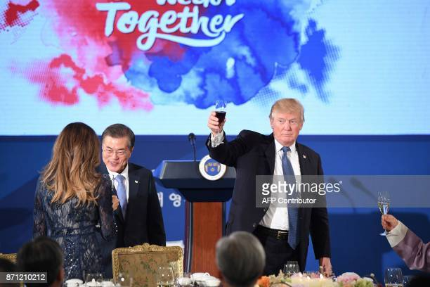US President Donald Trump holds a glass as South Korea's President Moon JaeIn talks to First Lady Melania Trump during a state dinner at the...