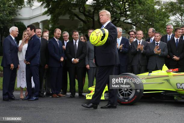 S President Donald Trump holds a helmet that was presented to him by Indianapolis 500 winner Simon Pagenaud during a ceremony at the White House on...