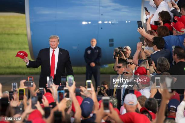 S President Donald Trump holds a Make America Great Again hat as he arrives for a 'Make America Great Again' campaign rally at Williamsport Regional...