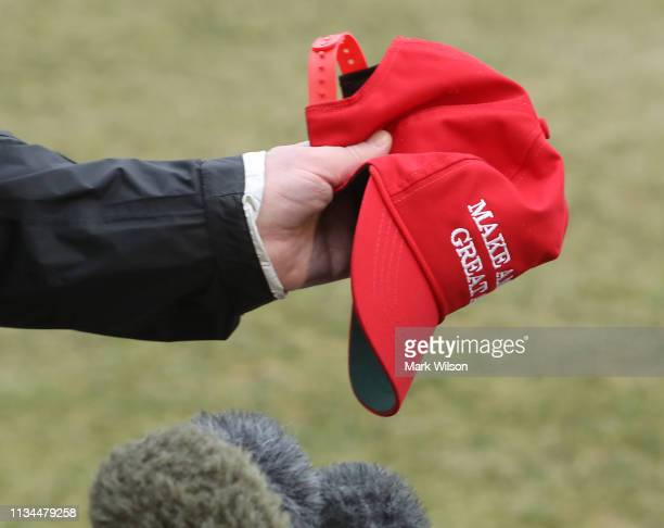 S President Donald Trump holds a Make America Great Again hat as he speaks to the media before departing from the White House on March 8 2019 in...