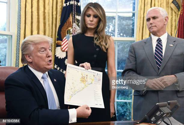 US President Donald Trump holds a map of the Texas Gulf Coast towards members of the media next to US First Lady Melania Trump center and US Vice...