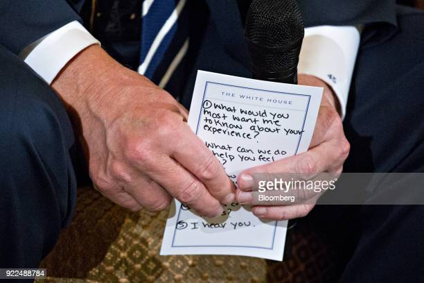 US President Donald Trump holds a note during a listening session on gun violence with high school students teachers and parents in the State Dining...
