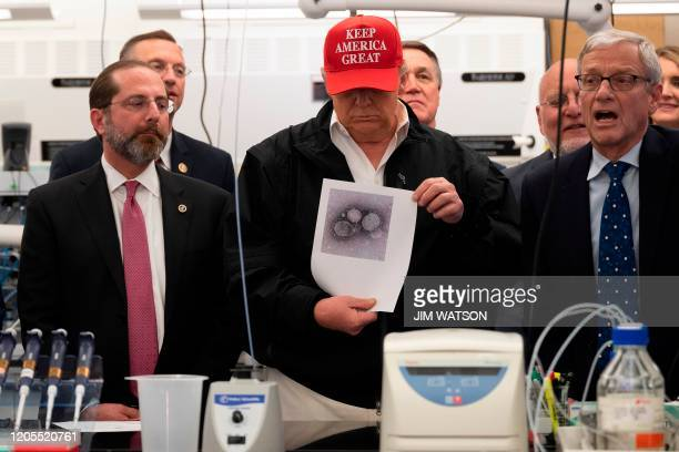President Donald Trump holds a picture of the coronavirus with US Health and Human Service Secretary Alex Azar , CDC Director Robert Redfield , and...