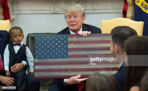 US President Donald Trump holds a plaque made by Brian Steorts the owner of Flags of Valor during a meeting with Steorts and other business owners...