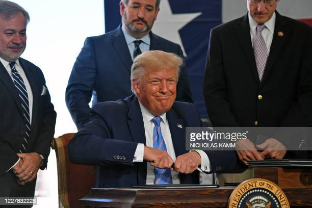 President Donald Trump holds a sharpie before signing several permits on restoring energy dominance in the Permian basin in Midland, Texas on July...