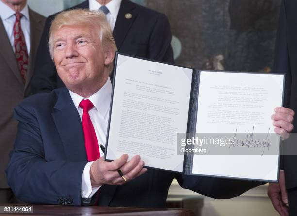 US President Donald Trump holds a signed memorandum addressing China's laws policies practices and actions related to intellectual property...
