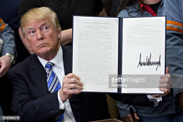 US President Donald Trump holds a signed proclamation on adjusting imports of aluminum into the United States in the Roosevelt Room of the White...